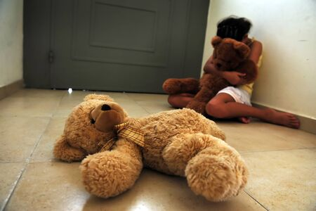 Photo pour Young girl victim of domestic violence sits on home floor hugging teddy bear. - image libre de droit