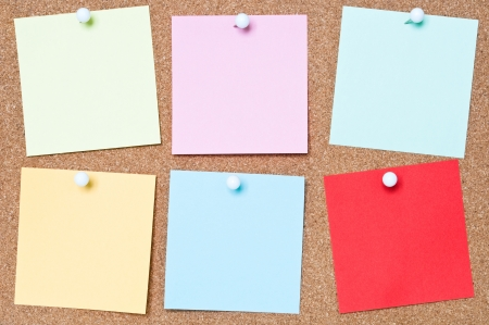 Selection of blank adhesive notes attached to a cork board