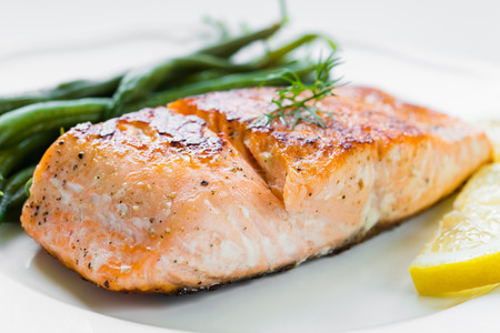 Close up of grilled salmon fillet with green beans and lemon on white plate