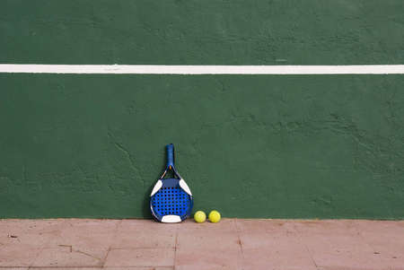 Two yellow tennis balls and a racket near the tennis wall