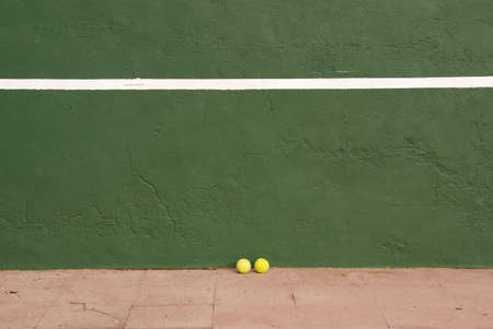 Two yellow tennis balls near the tennis wall