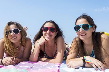 Photo pour smiling pretty girls best friends lying on beach while looking camera. - image libre de droit
