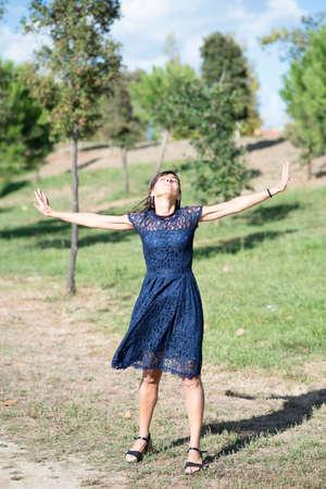 Photo pour Happy hispanic woman in blue dress and arms raised standing in a public city park - image libre de droit