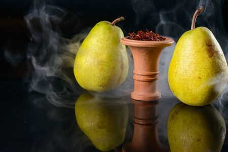 Fragrant pear tobacco for hookah in bowl on black glass background