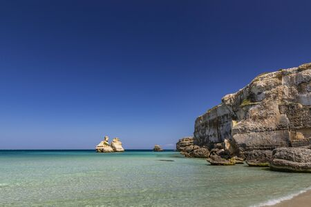 Photo pour The bay of Torre dell'Orso, with its high cliffs, in Salento, Puglia, Italy. Turquoise sea and blue sky, sunny day in summer. A beach of fine white and pink sand. The stacks called the Two Sisters. - image libre de droit