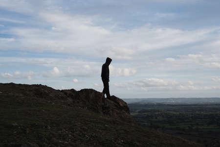 Photo pour A hooded figure walking towards the top of a rocky outcrop. Looking down across the landscape - image libre de droit