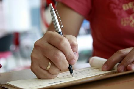 Photo pour woman signing a check cheque - image libre de droit