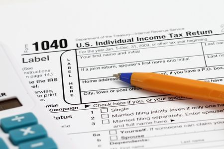 completing a 1040 tax form with calculator.