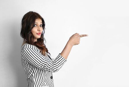 Attractive beautiful young Indian business woman pointing her finger gesture isolated on white background
