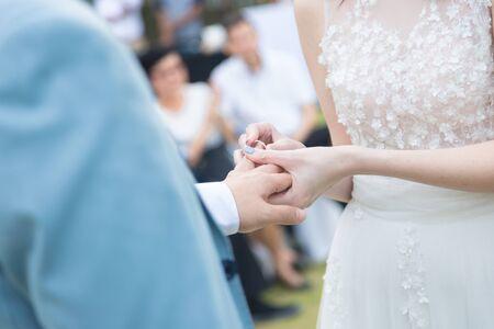 Foto de bride wearing ring to groom in wedding ceremony, lady hold man hand gently - Imagen libre de derechos