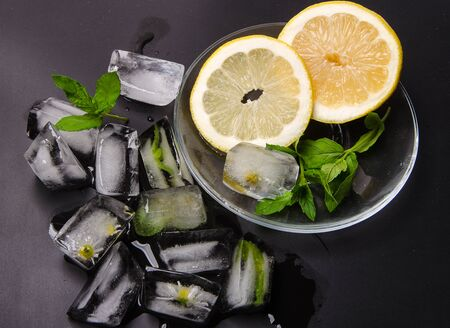 ice cubes with lemon and mint in dark