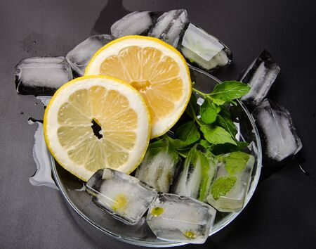 ice cubes in glass with lemon and mint in dark
