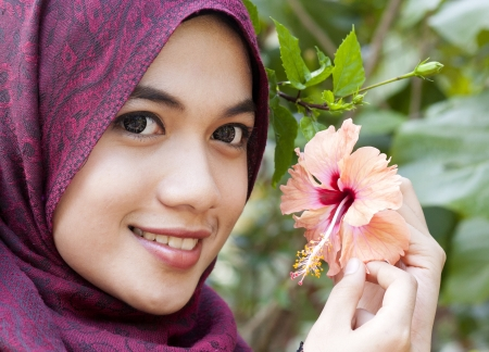 Young muslim woman holding a red hibiscus flower next to her faceの写真素材