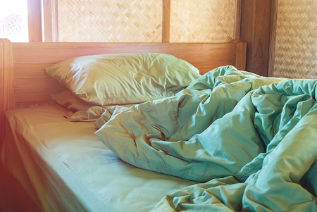 Photo pour green pillow and blanket with wrinkle messy on bed in vintage wooden bedroom with lighting upper left side, from sleeping in a long night winter. - image libre de droit