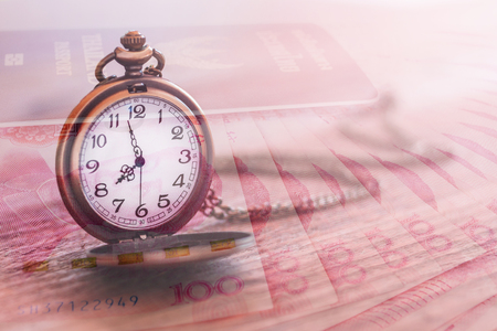pocket watch over yuan banknotes with double exposure effect, time is money, business and finance concept
