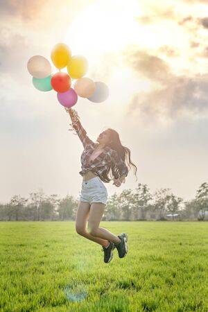 Photo for Portrait of a happy pretty woman with balloons in green field - Royalty Free Image
