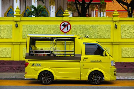 Photo pour PHUKET TOWN, THAILAND - JANUARY 4. 2019: Isolated yellow minibus tuk tuk in front of temple wall in the same color - image libre de droit