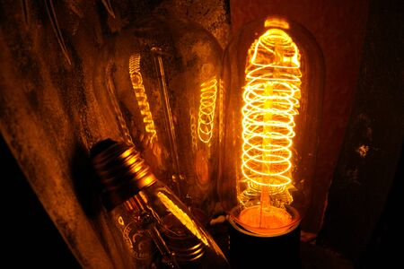 Photo for Cobbled classic incandescent Edison light bulbs with visible glowing wires in the night - Royalty Free Image