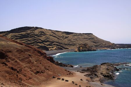 View on secluded lagoon surrounded by impressive rugged weathered cliffs in different colors - El Golfo, Lanzarote