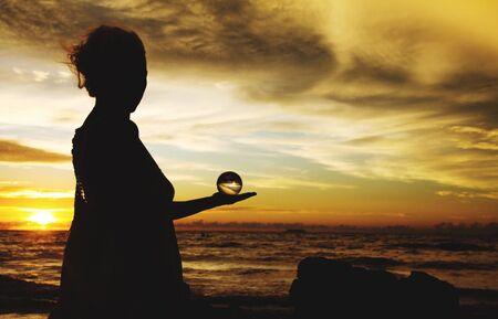 Photo pour Silhouette of woman holding crystal ball against horizon in the evening sun on Ko Lanta, Thailand - image libre de droit