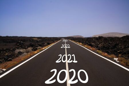 Photo pour Long hard stony successful way concept: view on endless asphalt road through dry arid volcanic landscape with numbers of years 2020, 2021, 2022, 2023 - image libre de droit