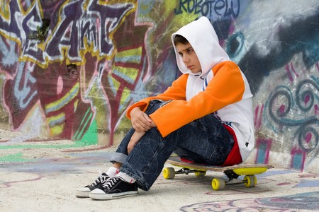 Angry teenager sitting on his skate near a graffiti wall
