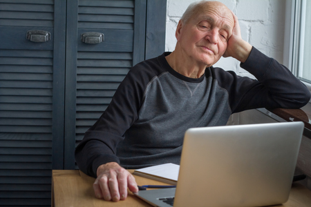 Photo pour An elderly man is tired of looking at the screen of an open laptop, counting taxes, selective focus, free space for text. - image libre de droit