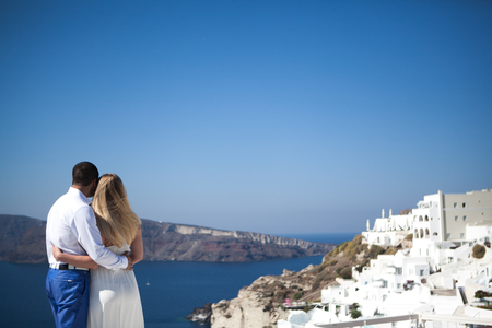 Foto de young couple pregnant on the most romantic island Santorini, Greece, view of Santorini. - Imagen libre de derechos