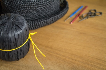 A skein of black yarn tied with a yellow thread next to a knitted black hat on a light wooden surface. Selective soft focus. Free space for text.