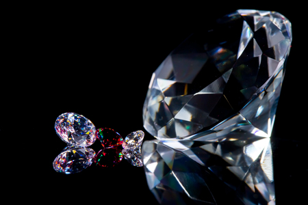 Photo pour Huge diamond and several chic crystals on a deep black mirror surface, shimmer and sparkle, free space for text. - image libre de droit