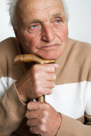 Photo pour Portrait of an old sad man who put his head on the handle of a wooden cane, the concept of loneliness at home. - image libre de droit