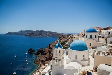 Photo for Oia town on Santorini island, Greece. View of traditional white houses and churches with blue domes over the Caldera, Aegean sea - Royalty Free Image