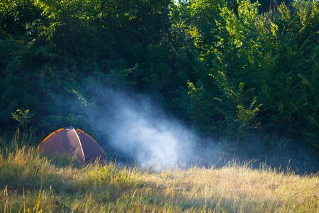 Photo pour Tourist tent and smoking bonfire in a field in front of the forest at sunrise, copyspace - image libre de droit