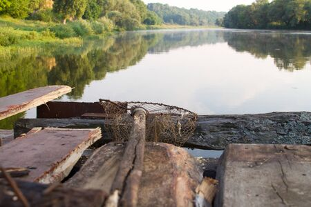 Photo pour Close up of an old home-made fishing landing net lies on an old wooden pier against the background of a wide river, selective focus - image libre de droit