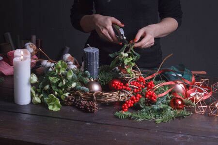 Photo for Close up of a female florist making a Christmas wreath of fir branches, Christmas bubbles and natural decor, selective focus - Royalty Free Image