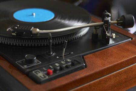 Closeup of blue music record on turntable, turntable needle playing music, selective focus