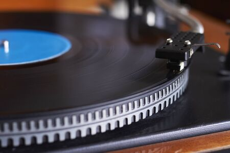 Extreme closeup of blue music record on turntable, turntable needle playing music, selective focus