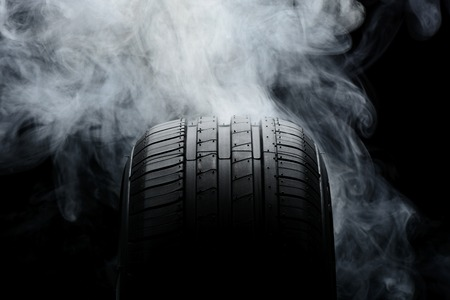 Car tire and smoke on black background