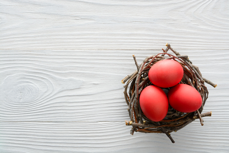 Photo for Easter background with red eggs in the nest on wooden table. Top view with copy space - Royalty Free Image