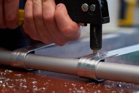 Photo pour Close-up male hand holds a riveter and rivets aluminum profiles - image libre de droit