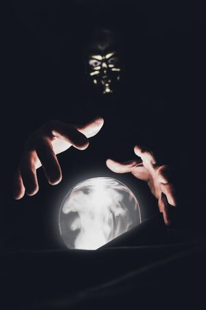 Photo pour A clairvoyant man in a mask of a skull holds his hands over a magic crystal ball. - image libre de droit
