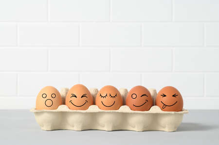 Photo pour Easter holiday concept with emotional chicken eggs in a tray. Eggs with funny faces in the package on white background. Different grimaces drawn on chicken eggs. Copy space - image libre de droit