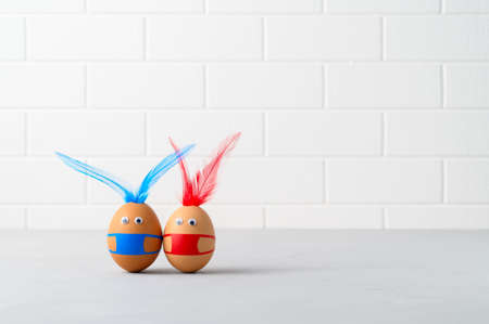 Photo pour Coronavirus Easter concept. Two brown easter eggs wearing protection face mask and feather ears for Easter holidays decoration. Selective focus with copy space - image libre de droit