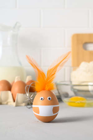 Photo pour Homemade Easter baking and stay at home. Brown easter rabbit made from egg wearing a protective face mask and feather ears on the kitchen table. Copy space. Ingredients and kitchen items for baking - image libre de droit