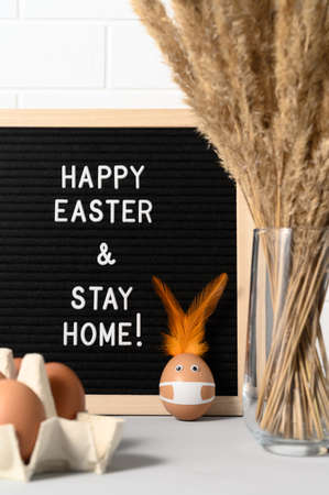 Photo pour Easter holiday concept 2021. Vase with dry canes, Easter eggs, and black felt letter board with slogan - Happy Easter and Stay Home on white brick wall background - image libre de droit