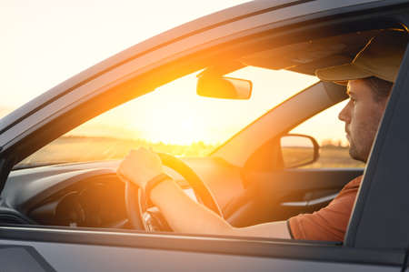 Photo for Caucasian Man in automobile in the countryside and sun rays. Male driver driving a car at sunset background. Summer travel, road trip and vacations concept - Royalty Free Image