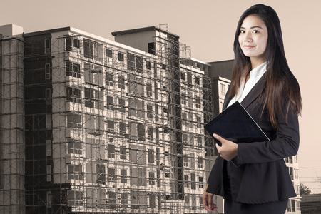 building, developing, construction and architecture concept - smiling woman
