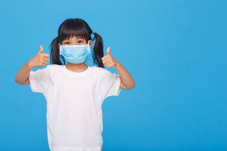 Photo for Coronavirus Covid-19 pm2.5.Online education.Little girl wearing face mask show thumbs up for good and happy at home. Covid-19 coronavirus.Stay home.Social distancing.New normal behavior. - Royalty Free Image