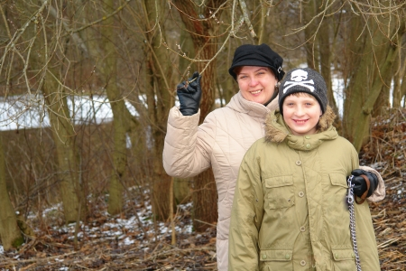 Happy mother and son walking in the winter forest