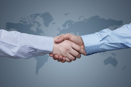 Business handshake with world map in the background